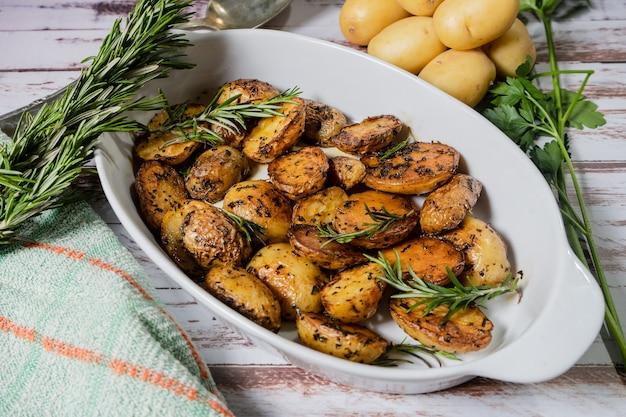 Piatto bianco ovale con deliziose patate arrosto con erbe fresche e naturali vista di taglio