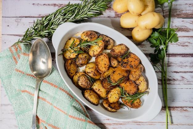 Piatto bianco ovale con deliziose patate arrosto con erbe fresche e naturali vista dall'alto