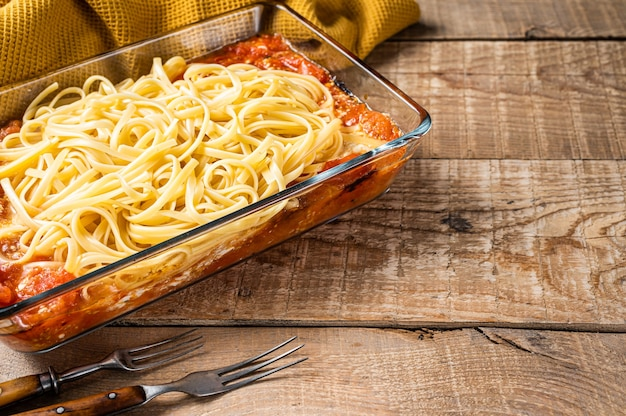 Feta al forno spaghetti in teglia. fondo in legno. vista dall'alto. copia spazio.