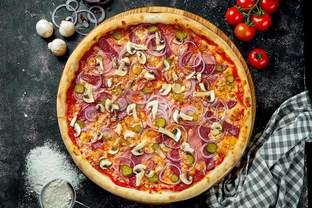 Pizza italiana cotta al forno con salsa rossa, formaggio, salame, prosciutto e funghi in una composizione con ingredienti su un tavolo scuro. vista dall'alto
