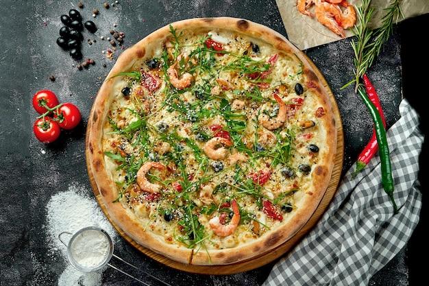 Pizza italiana cotta al forno con salsa, formaggio, rucola, gamberetti e olive in una composizione con ingredienti su un tavolo scuro. vista dall'alto pizza con frutti di mare