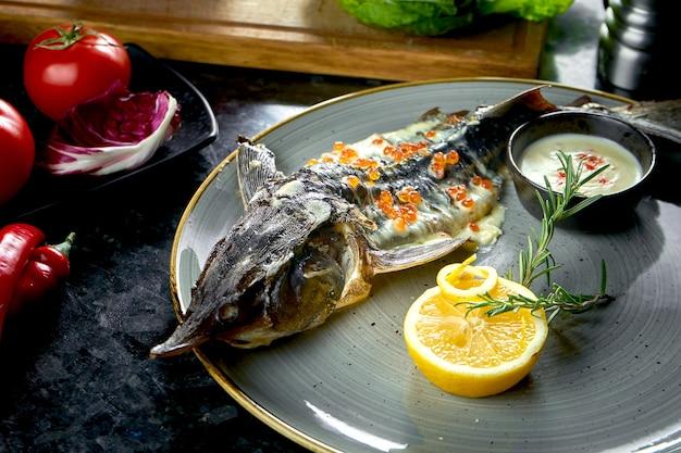 Sterlet al forno con salsa bianca e caviale rosso, servito in un piatto grigio su un tavolo di marmo scuro. cibo del ristorante. frutti di mare