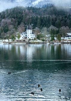 Coperto inverno lago alpino grundlsee vista con casa bianca (austria)