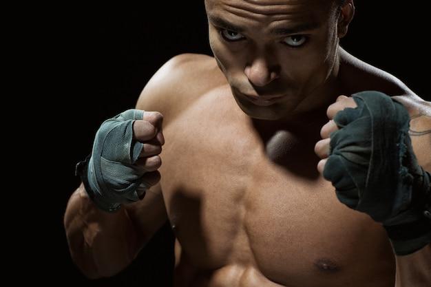 Supera la tua rabbia. colpo del primo piano di un giovane combattente professionista in posa che sembra serio con i pugni in alto