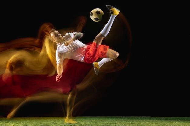 Superamento. giovane calciatore maschio caucasico o calciatore in abbigliamento sportivo e stivali che calcia la palla per l'obiettivo in luce mista sulla parete scura. concetto di stile di vita sano, sport professionistico, hobby.