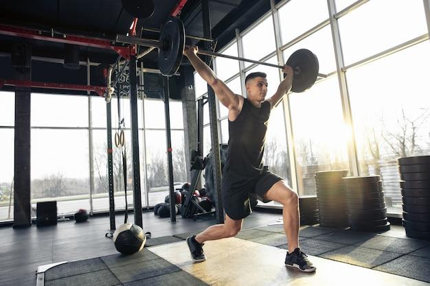 Superare. giovane atleta caucasico muscolare che si allena in palestra, fa esercizi di forza, pratica, lavora sulla parte superiore del corpo con pesi e bilanciere. fitness, benessere, concetto di stile di vita sano.