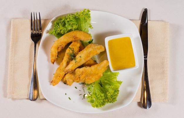 Sovraccarico di bastoncini di pollo con salsa di senape al miele sul piatto al coperto
