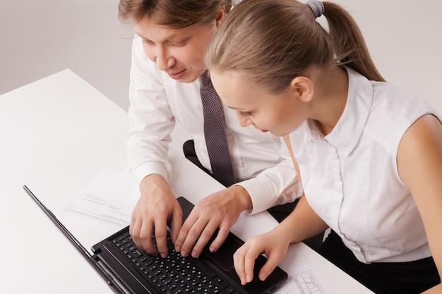 Primo piano sopraelevato delle coppie di affari facendo uso del computer portatile. isolato su sfondo bianco.