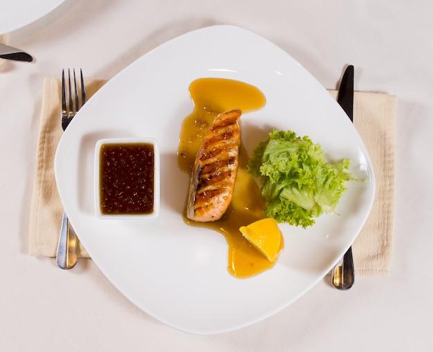 Sovraccarico di pesce alla griglia su piastra con salsa di immersione