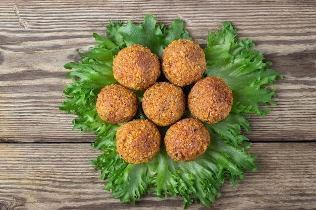 Immagine aerea di falafel arabo spuntino sotto forma di palline di ceci con spezie. fondo in legno.