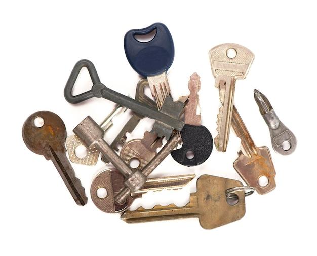 Sovraccarico di molte chiavi diverse in oder su un concetto di sfondo bianco