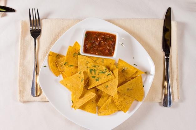 Sovraccarico di patatine nacho e salsa sul piatto al posto sul tavolo