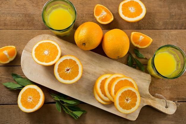 Sovraccarico di arance con bicchieri di succo sul tavolo di legno