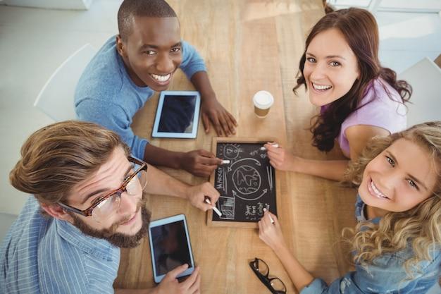 Ritratto sopraelevato della gente di affari sorridente che scrive i termini di affari sull'ardesia