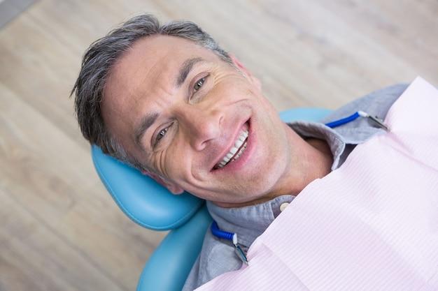 Ritratto ambientale dell'uomo sorridente che si siede sulla sedia
