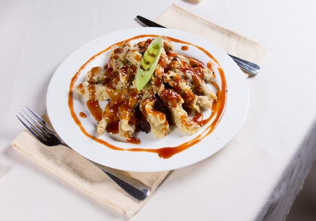 Sovraccarico di saucy tempura dish al place setting in restaurant