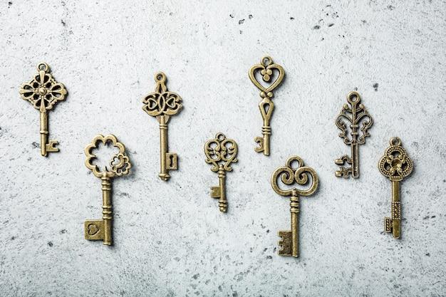 Tiro ambientale di molte vecchie chiavi differenti sulla vecchia superficie di cemento grigio. concetto con copia spazio