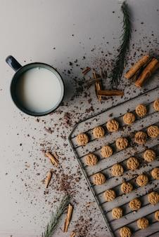 Scatto dall'alto della griglia di cottura con deliziosi biscotti rotondi al cioccolato e una tazza di latte