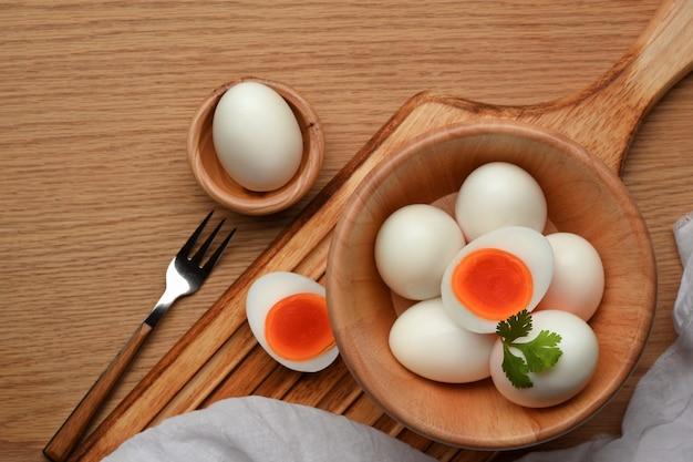 Scatto dall'alto di una ciotola di uova sode sulla tovaglietta sul tavolo per la colazione, pasto della colazione heathy