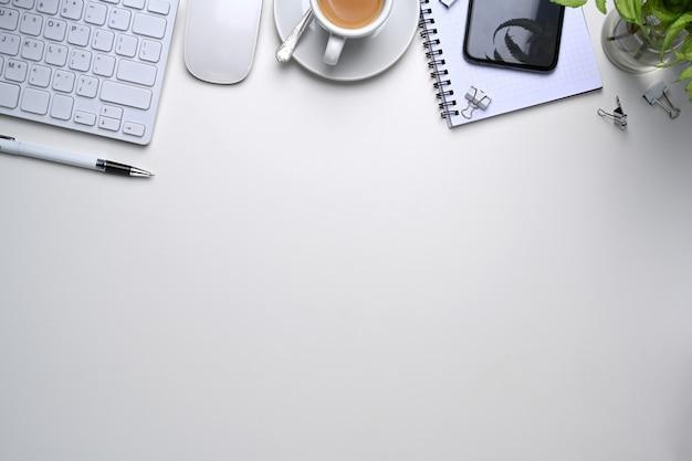 Scatto dall'alto di un ambiente di lavoro confortevole con smart phone, tastiera, pianta, notebook e copia spazio su sfondo bianco.