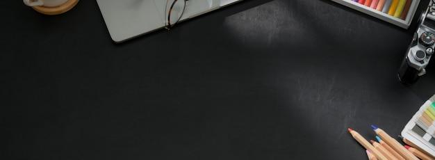 Colpo ambientale dell'area di lavoro del progettista con gli strumenti della pittura, il computer portatile, la macchina fotografica e lo spazio della copia