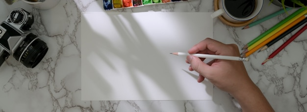 Colpo sopraelevato dell'artista maschio che attinge la carta di schizzo con gli strumenti della pittura