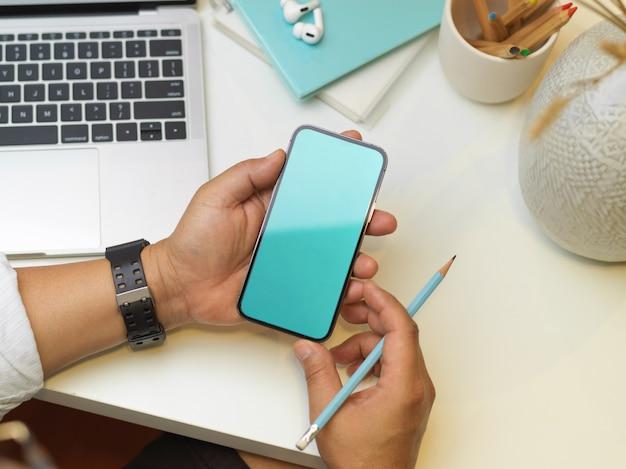 Scatto dall'alto delle mani maschili utilizzando smartphone su area di lavoro con laptop, cancelleria e custodia per piante