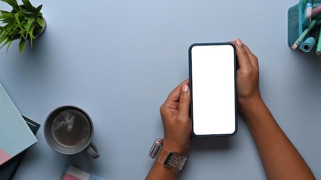 Colpo dall'alto delle mani dell'uomo che tengono finto smartphone sul tavolo blu. schermo vuoto per il tuo messaggio di testo o contenuto informativo.