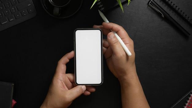 Colpo ambientale del fotografo che per mezzo dello smartphone dello schermo in bianco con lo stilo