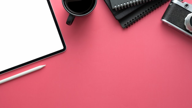 Colpo ambientale dell'area di lavoro del fotografo con la compressa digitale e articoli per ufficio sulla tavola rosa