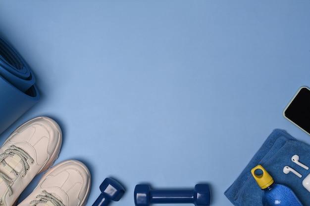 Scatto dall'alto di scarpe, smartphone, bottiglia d'acqua, manubri, auricolari e tappetino blu su sfondo blu.