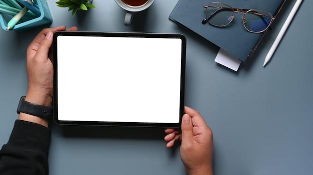 Scatto dall'alto delle mani dell'uomo alla moda che tengono mock up tablet digitale con schermo vuoto sul tavolo grigio con diario, bicchieri e tazza di caffè.