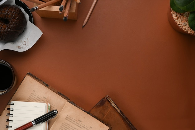 Scatto dall'alto del posto di lavoro vintage con tazza di caffè, taccuino, libro e copia spazio in pelle marrone.