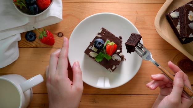 Colpo sopraelevato di una donna che mangia il brownie del cioccolato sul piatto bianco