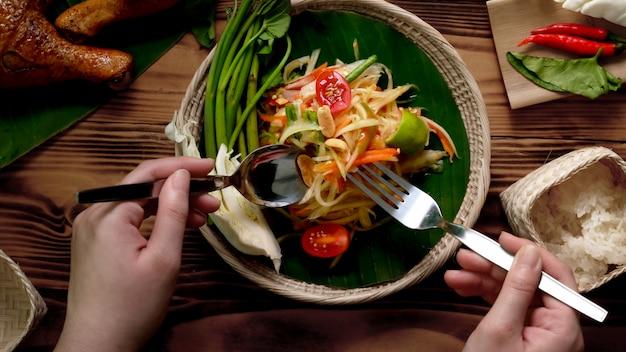 Colpo sopraelevato della donna che mangia somtum, alimento tradizionale tailandese con pollo grigliato e riso appiccicoso