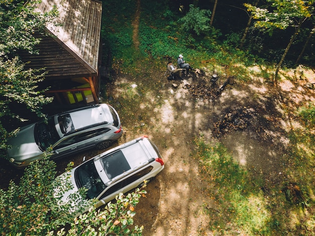 Vista dall'alto del barbecue nella foresta due auto suv parcheggiate?