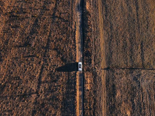 Vista dall'alto dell'auto che passa per il campo di fattoria su strada