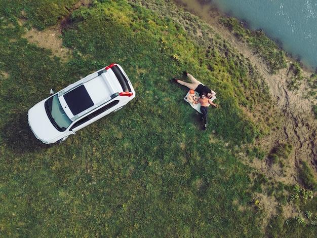 Vista dall'alto dell'auto suv e coppia sdraiata su una coperta allo spazio copia della spiaggia del fiume