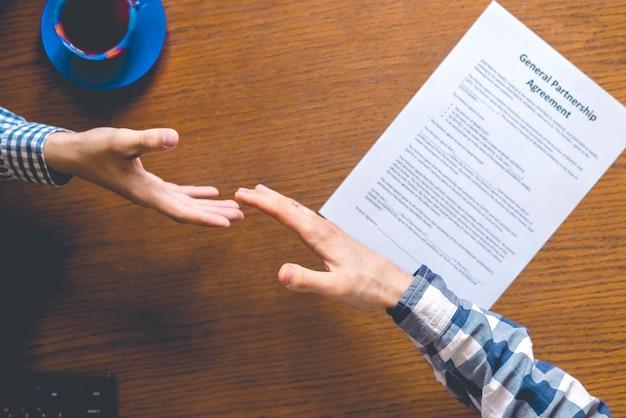 Vista dall'alto di due lavoratori in casual in ufficio a firmare l'accordo di contratto sul tavolo