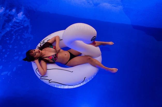 Vista dall'alto di una bella ragazza seria che galleggia su un cigno galleggiante in piscina.