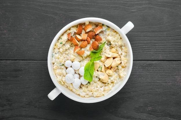 Vista dall'alto del porridge di bulgur con mandorle e nocciole e mirtilli rossi in panatura di zucchero pouder