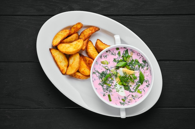 Vista dall'alto della zuppa fredda di barbabietola con spicchi di patate su un piatto
