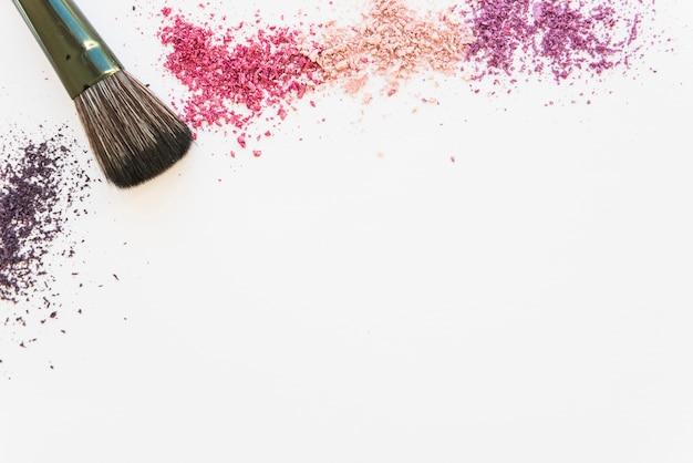 Una vista aerea di cosmetici colorati in polvere e make-up pennello su sfondo bianco