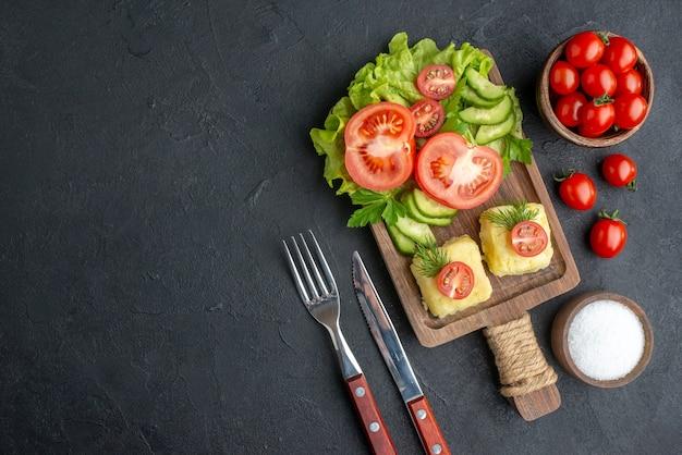 Vista dall'alto di pomodori freschi tagliati e formaggio di cetrioli su tavola di legno posate su superficie nera