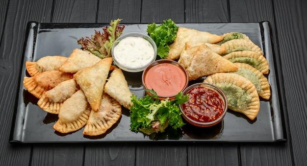 Vista dall'alto di fagottini fritti o chebureki con ripieno di carne di manzo macinata e cipolla