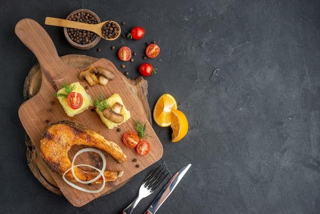 Vista dall'alto di deliziosi pesci fritti e funghi pomodori verdi su tagliere di legno posate pepe su superficie nera