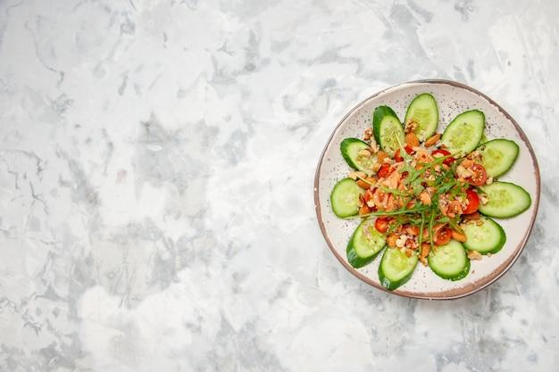 Vista dall'alto di una deliziosa insalata decorata con cetriolo tritato e verdure sul lato sinistro su una superficie bianca macchiata con spazio libero