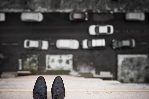 Una vista dall'alto di un uomo depresso o instabile in piedi sul bordo del tetto di una casa alta