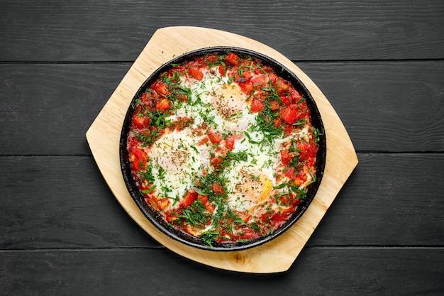 Vista dall'alto di uova fritte con prosciutto e pomodoro in padella in ghisa