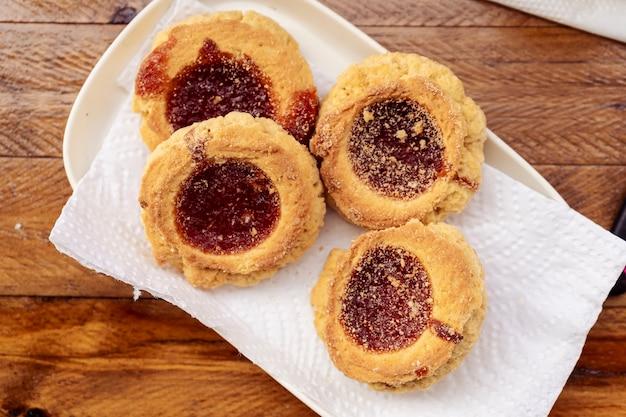 Vista dall'alto di quattro biscotti al burro fatti in casa con marmellata. concetto di cibo fatto in casa e naturale. orientamento orizzontale.
